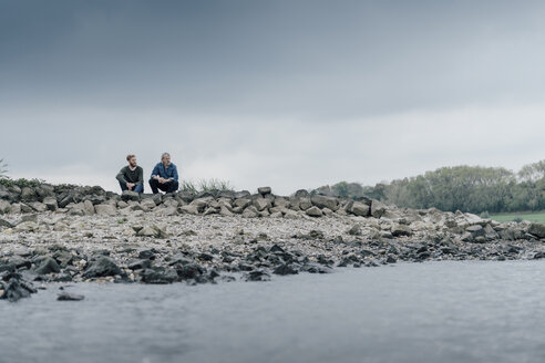 Father and son sitting at the river, talking together - KNSF02958