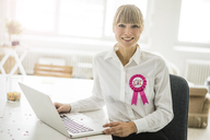 Portrait of smiling businesswoman with laptop in office celebrating her birthday - JOSF01949
