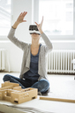 Woman in office with architectural model wearing VR glasses - JOSF01958