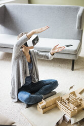 Woman in office with architectural model wearing VR glasses - JOSF01967