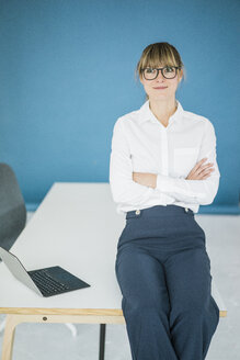 Portrait of smiling businesswoman with laptop in office - JOSF01970
