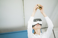 Businesswoman wearing VR glasses holding cubical structure - JOSF01976