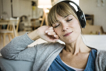 Relaxed woman with closed eyes listening to music with headphones - JOSF02003