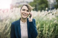 Smiling businesswoman on cell phone outdoors - JOSF02006