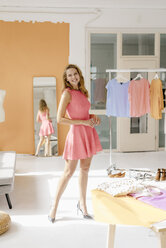 Portrait of smiling young woman in fashion studio - KNSF02971