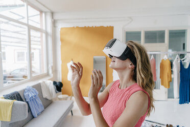 Young woman in fashion studio wearing VR glasses - KNSF02983