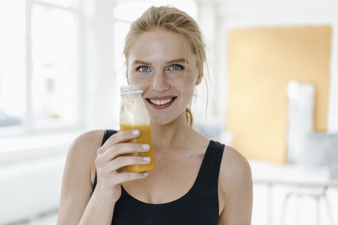 Portrait of smiling young woman in sportswear drinking a smoothie - KNSF03007