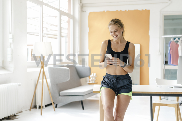 Smiling young woman in sportswear looking at cell phone - KNSF03013