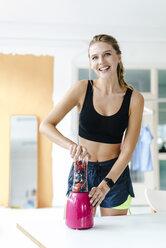 Portrait of happy young woman in sportswear blending fruit - KNSF03022