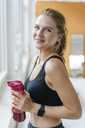 Portrait of smiling young woman in sportswear drinking a smoothie - KNSF03025