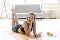 Smiling young woman in sportswear lying on gym mat listening to music - KNSF03028