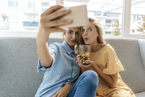 Two young women sitting on couch taking a selfie with sweets - KNSF03040