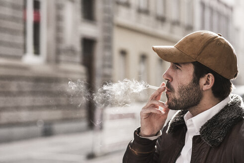 Portrait of young man with baseball cap smoking cigarette - UUF12323