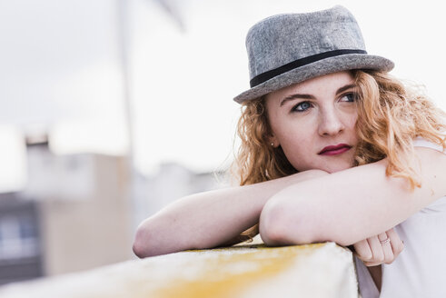 Portrait of strawberry blonde young woman wearing hat leaning on balustrade - UUF12326
