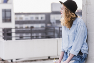 Content young woman wearing hat relaxing on roof terrace - UUF12335