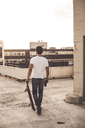 Back view of young man with skateboard and beer bottle on roof terrace at evening twilight - UUF12347