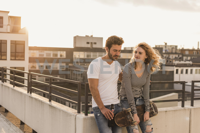Young couple relaxing on roof terrace at sunset - UUF12350