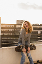 Portrait of cheeky young woman with skateboard on roof terrace at sunset - UUF12353