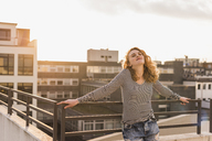 Young woman enjoying sunset on roof terrace - UUF12356