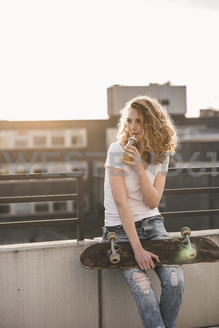 Young woman with skateboard drinking beverage on roof terrace at sunset - UUF12359