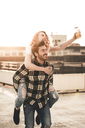 Happy young couple on roof terrace at sunset - UUF12362