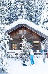 Austria, Altenmarkt-Zauchensee, woman decorating Christmas tree at hut - HHF05528