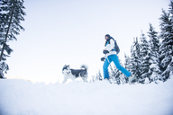 Austria, Altenmarkt-Zauchensee, young woman with dog in winter forest - HHF05537