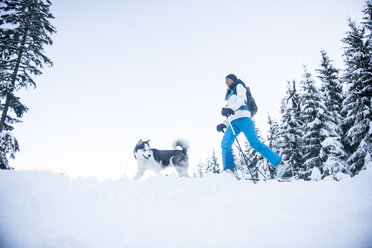 Austria, Altenmarkt-Zauchensee, young woman with dog in winter forest - HHF05537