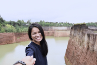 Thailand, Chiang Mai, happy young woman holding hand of her partner at grand canyon - IGGF00198