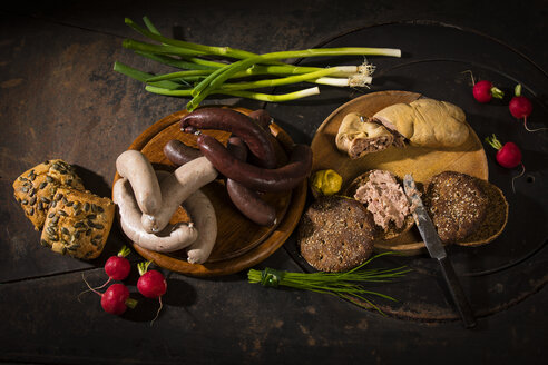 Liver sausage, blood sausage,  spring onion, red radish, chives, mustard, bread on chopping board, hotplate - MAEF12458