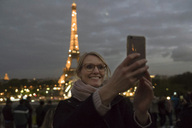 France, Paris, portrait of happy woman taking selfie with lighted Eiffel Tower in the background - CHPF00449