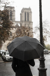 France, Paris, woman with umbrella in front of Notre Dame de Paris - CHPF00452