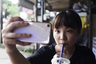 Portrait of woman drinking smoothie while taking selfie with smartphone - IGGF00222