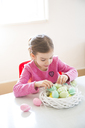 Girl arranging coloured Easter egg in Easter nest - LVF06433