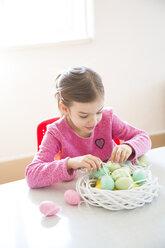 Girl arranging coloured Easter egg in Easter nest - LVF06433