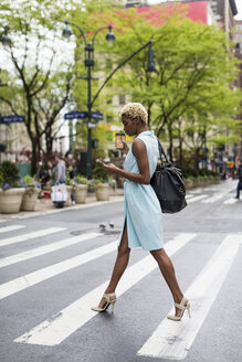 USA, New York, young blonde african-american woman with cup of coffee and smart phone crossing street - MAUF01239