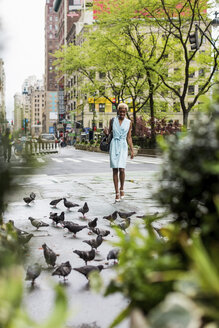 USA, New York, young blonde african-american woman walking on street, pigeons - MAUF01242