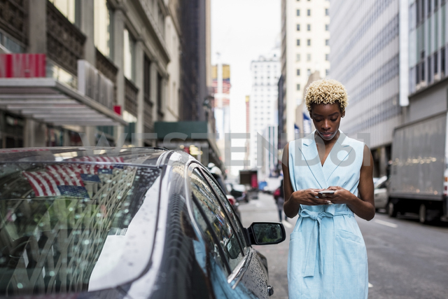 USA, New York, young blonde african-american woman using smartphone - MAUF01251 - Mauro Grigollo/Westend61