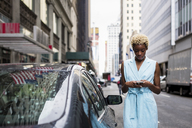 USA, New York, young blonde african-american woman using smartphone - MAUF01251