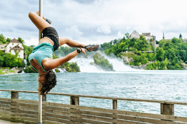 Switzerland, Schaffhausen, woman doing pole dance posture at the Rhine Falls - KIJF01716