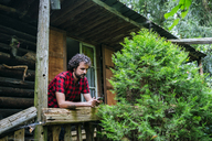 France, Strasbourg, man typing on mobile phone in old wooden hut - KIJF01731