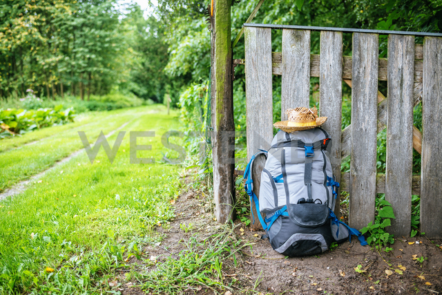 France, Strasbourg, travel backpack and straw hat in front of wooden fence on the way - KIJF01734 - Kiko Jimenez/Westend61