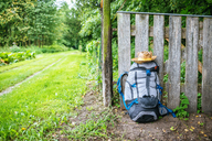 France, Strasbourg, travel backpack and straw hat in front of wooden fence on the way - KIJF01734
