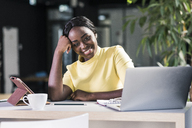 Smiling businesswoman with laptop and tablet - UUF12374