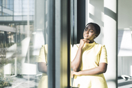 Businesswoman looking out of the window in office - UUF12383
