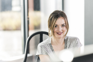 Portrait of smiling businesswoman at desk in office - UUF12401