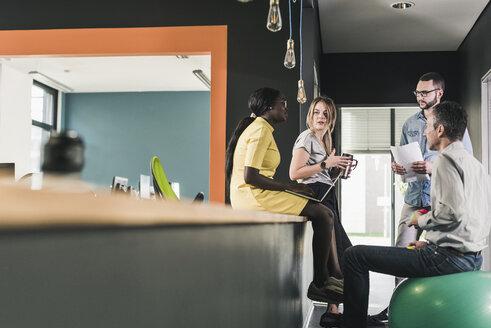 Business people having an informal meeting in office - UUF12413