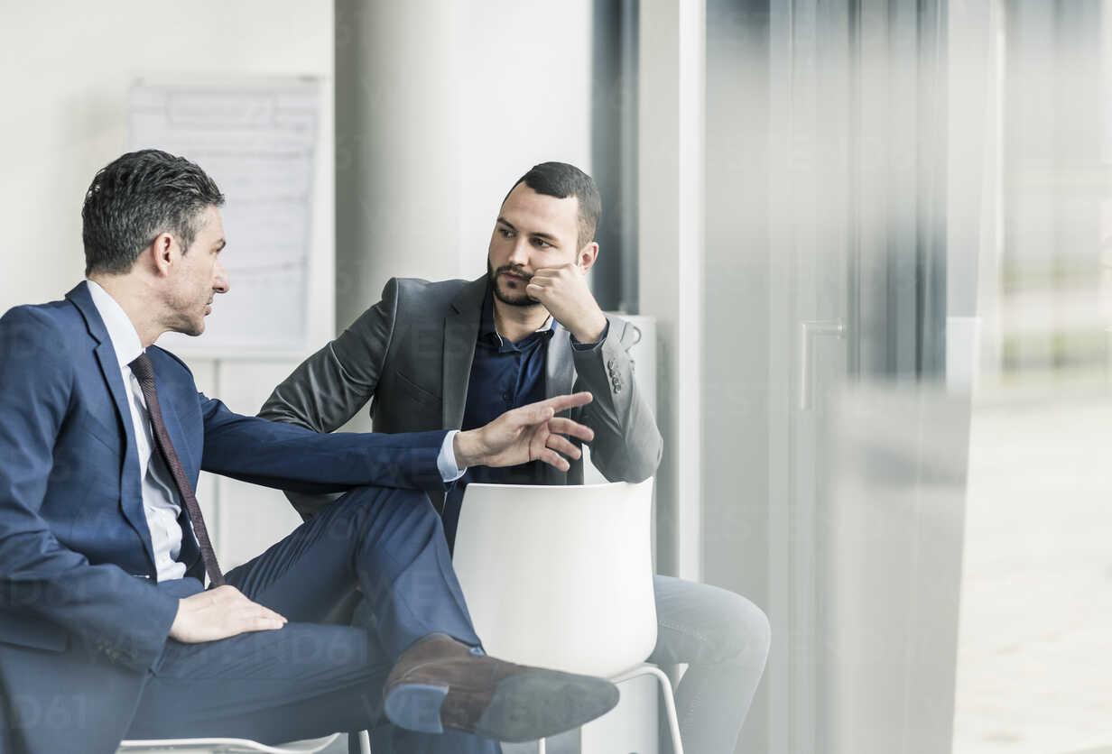 Two businessmen talking in office at the window - UUF12419 - Uwe Umstätter/Westend61