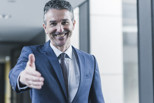 Portrait of smiling businessman about to shake hands - UUF12431