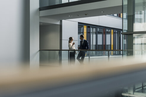 Businessman and businesswoman talking on office floor - UUF12434